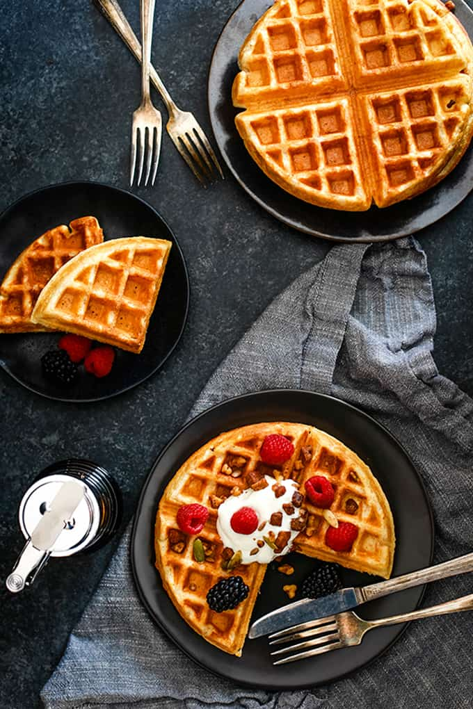 An overhead view of three plates, each with a Yogurt Waffle resting on top.
