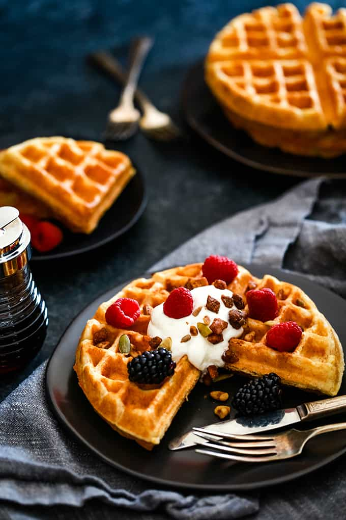 A piece of a Yogurt Waffle is missing as it sits on a dark plate with a fork and knife.
