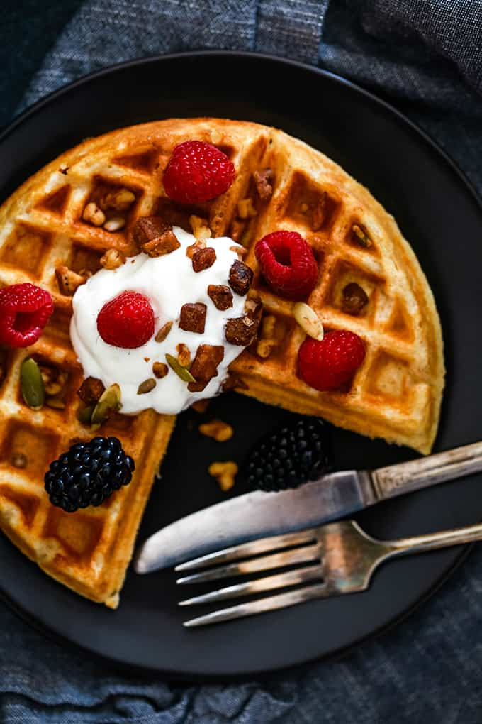 A section of a Yogurt Waffle is removed as it rests on a dark plate with a fork and knife.