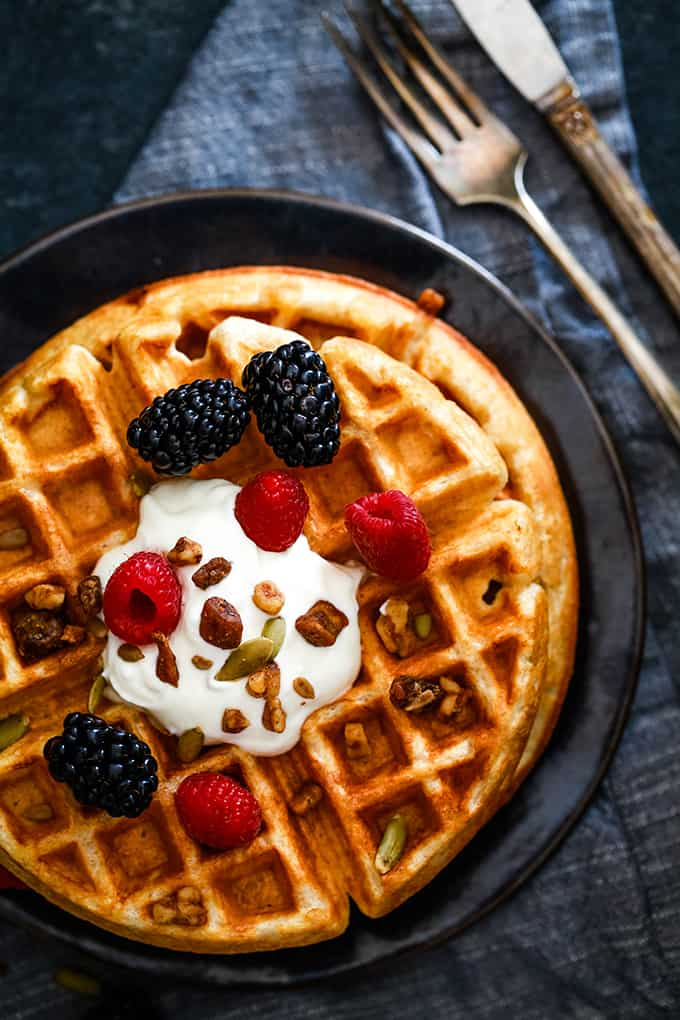 Two Yogurt Waffles are covered with a dollop of yogurt, fresh berries and granola.