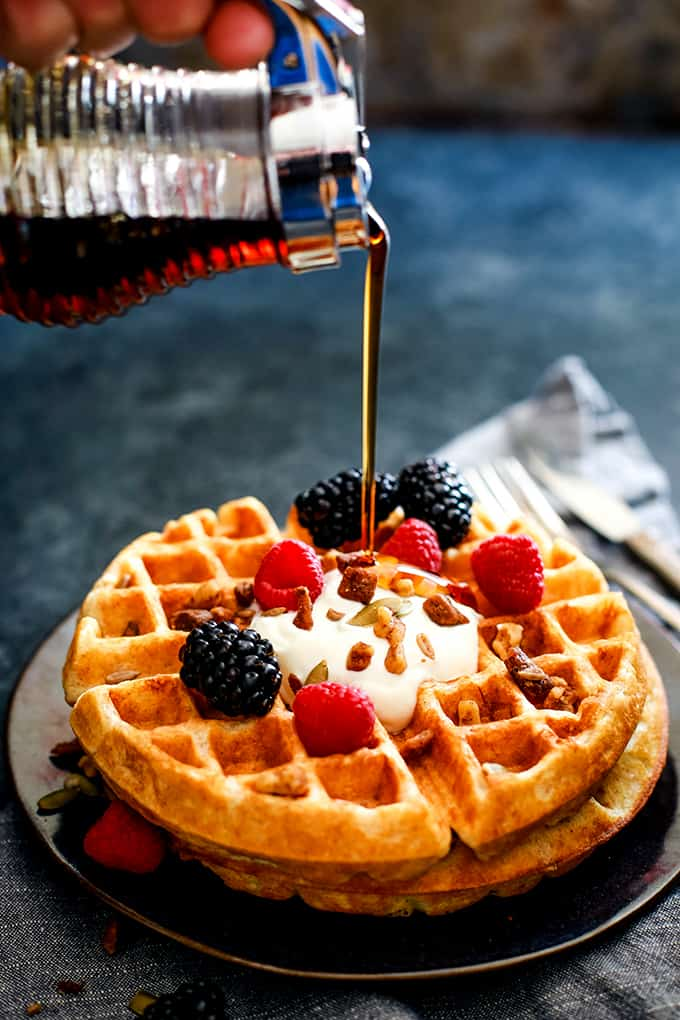 A hand pours syrup over the top of a Yogurt Waffle.