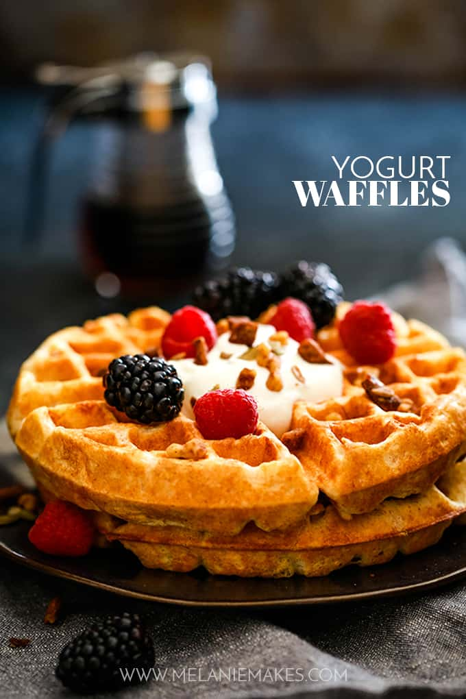 Two Yogurt Waffles are stacked on a plate and topped with a dollop of yogurt and fresh berries.