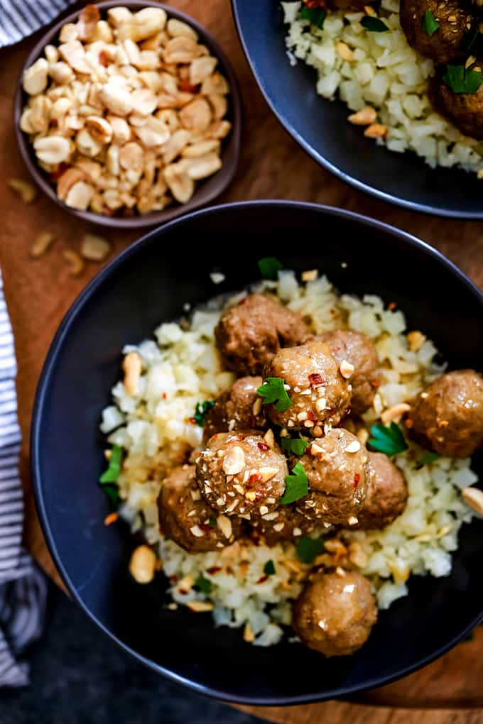 An overhead view of a bowl of Slow Cooker Thai Chili Peanut Meatballs with a small bowl of peanuts to garnish.