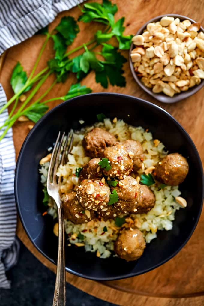 A black bowl of Slow Cooker Thai Chili Peanut Meatballs sits on a wooden tray.