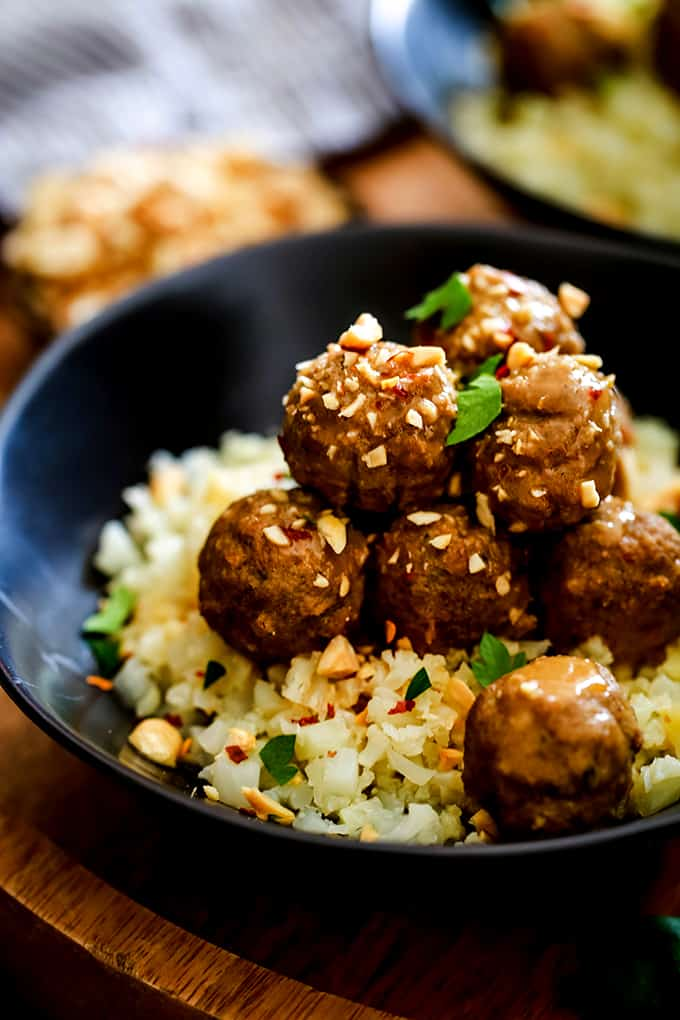A bowl of Slow Cooker Thai Chili Peanut Meatballs garnished with chopped peanuts and cilantro.