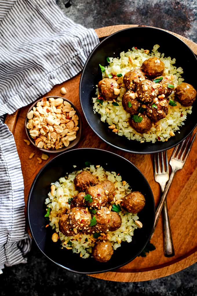 Two bowls of Slow Cooker Thai Chili Peanut Meatballs sit on a wooden tray flanked by a striped napkin.