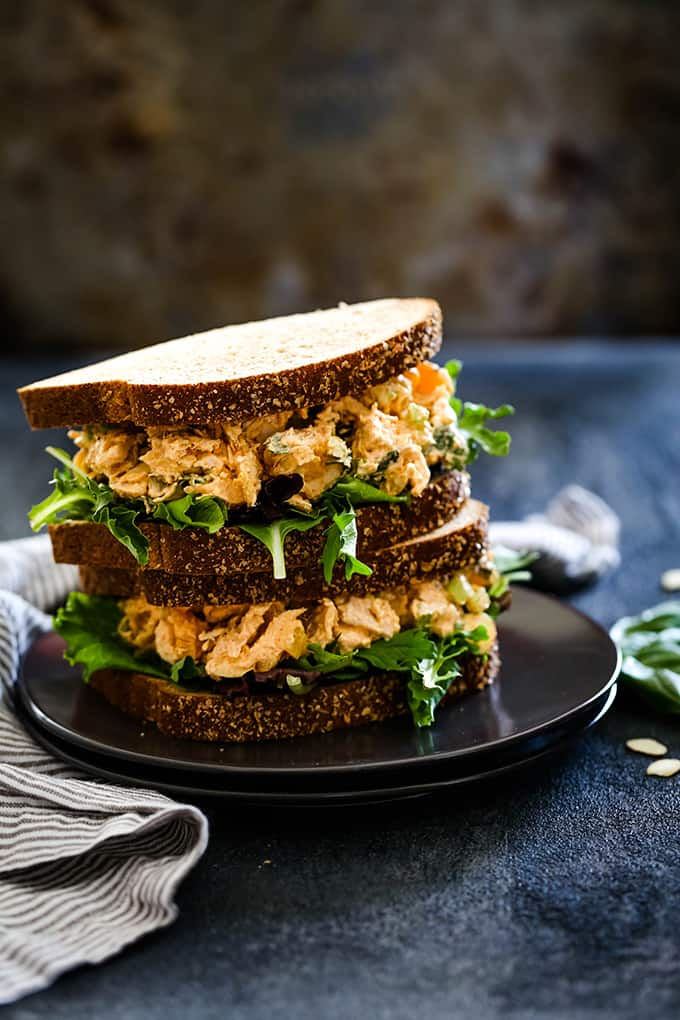 Two Apricot Basil Chicken Salad sandwiches are stacked on a dark plate.