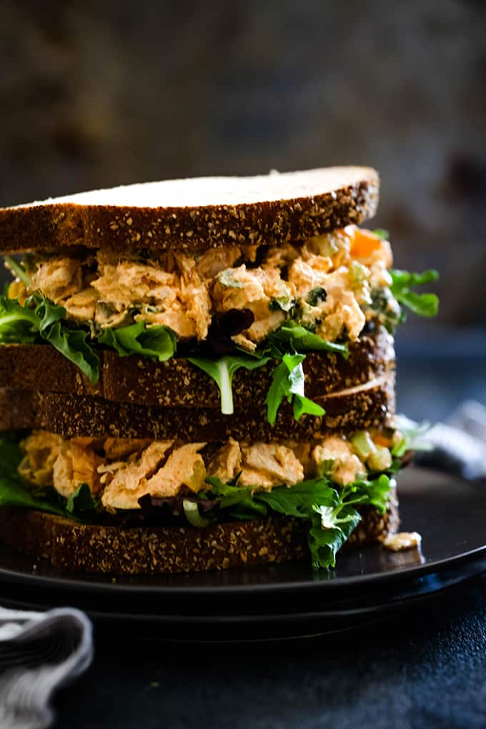 Two stacked sandwiches stuffed with Apricot Basil Chicken Salad and arugula.