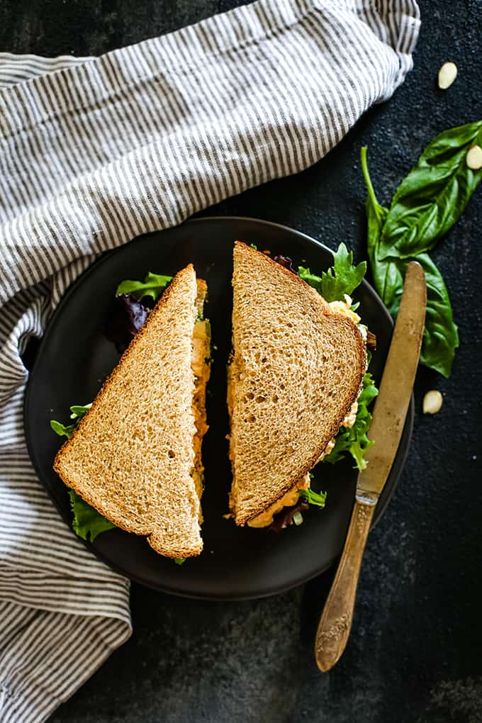 An overhead view of a sliced Apricot Basil Chicken Salad Sandwich on a plate with a knife.