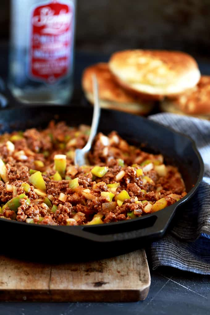 A skillet of Easy Sloppy Joes with a spoon sits on a wooden serving board.