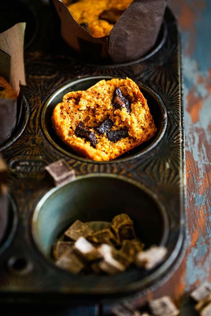 Half of a Pumpkin Chocolate Chip Muffin rests in a metal muffin tin.