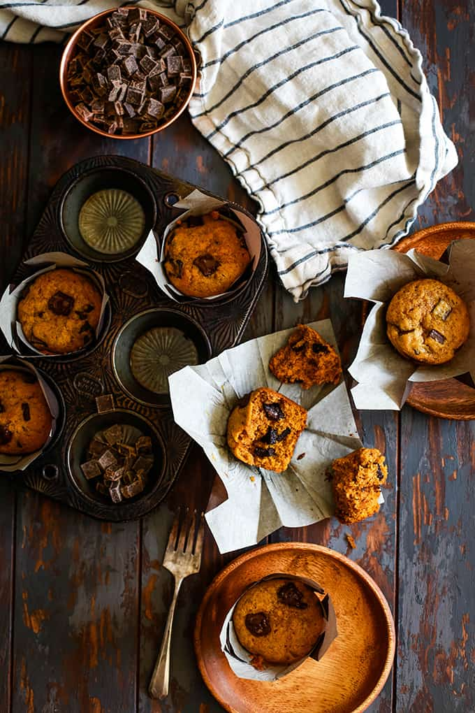 A muffin tin with Pumpkin Chocolate Chip Muffins as well as wooden plates and a striped town sit on a chipped wooden table.