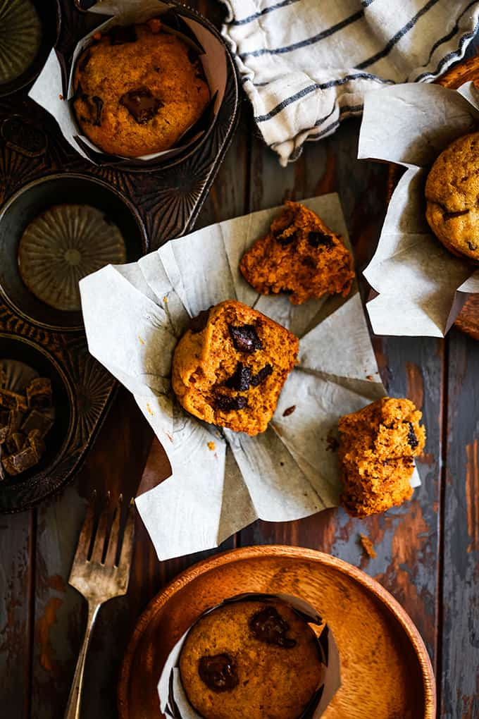 Half of a Pumpkin Chocolate Chip Muffin sits on a paper wrapper surrounded by a muffin tin, striped towel and wooden plate.