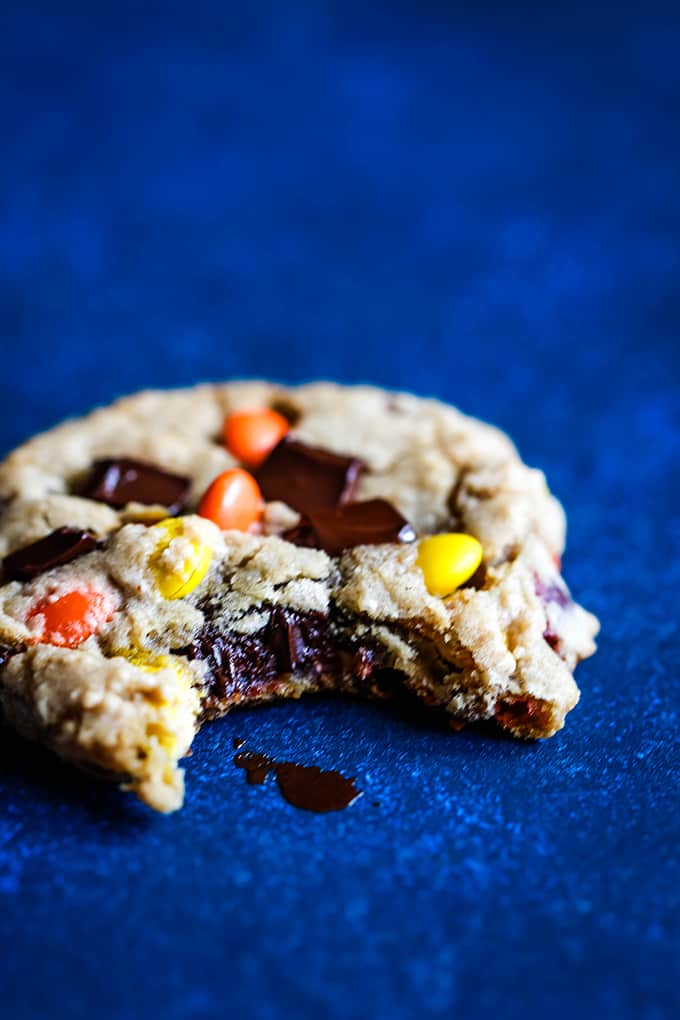 A Reese's Pieces Chocolate Chip Cookie with a bite taken out of it on a blue background.