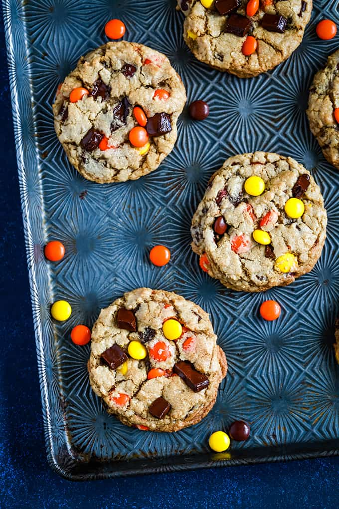 Reese's Pieces Chocolate Chip Cookies on a baking sheet surrounded by additional pieces of candy.