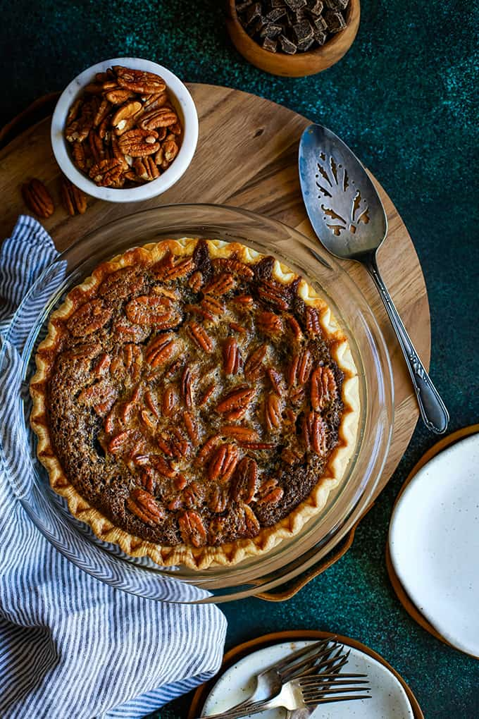 A Dark Chocolate Brownie Pie sits on a wooden tray surrounded by bowls of pecans and chocolate, a pie server, a striped napkin and plates and forks.