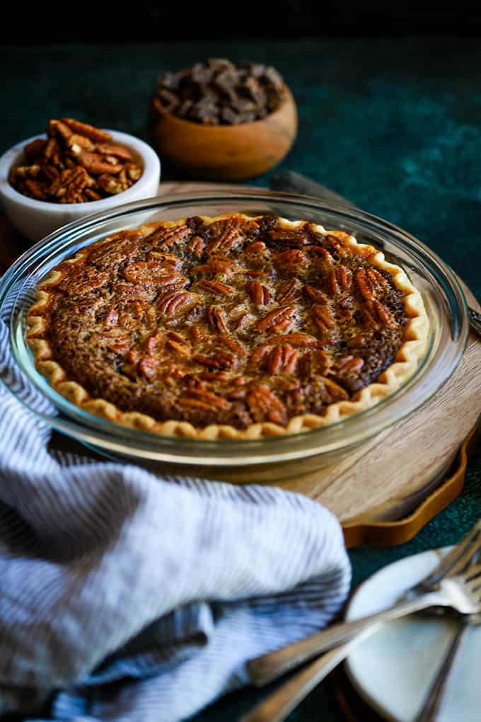 A Dark Chocolate Brownie Pie sits on a wooden tray surrounded by bowls of pecans and chocolate, a striped napkin and plates and forks.