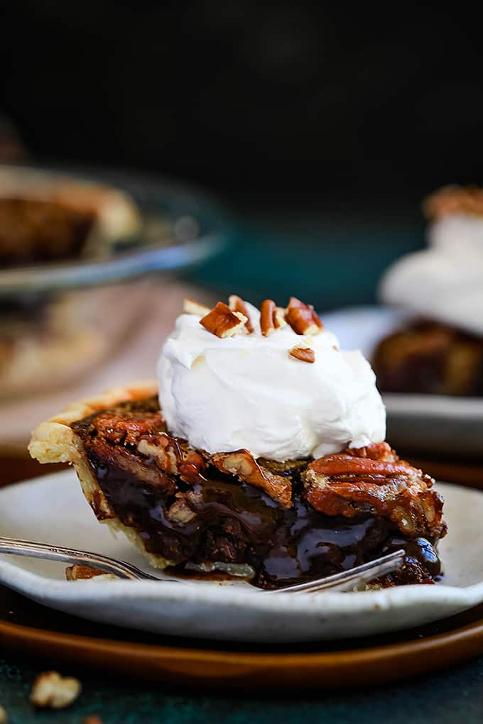 A slice of Dark Chocolate Brownie Pecan Pie sits on a white plate with a fork on a wooden charger.