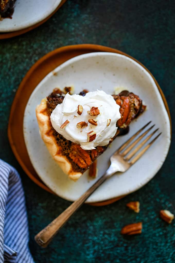 An overhead shot of a slice of Dark Chocolate Brownie Pecan Pie sitting on a white plate on a wooden charger with a fork on the plate and surrounded by a striped napkin, additional pecans and a second plate.