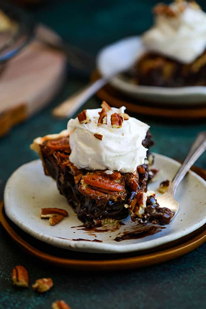 A slice of Dark Chocolate Pecan Pie sits on a white plate with a bite removed. The plate since in front of another plate and a wooden tray.