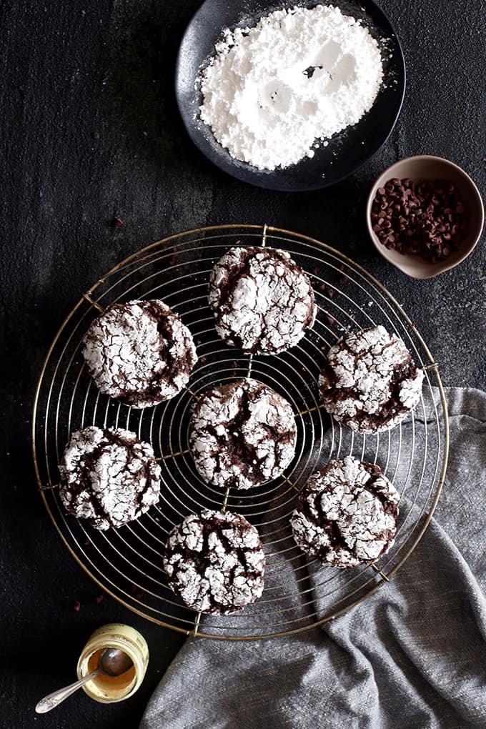 Double Chocolate Ginger Crinkle Cookies rest on a wire cooling rack surrounded by bowls of powdered sugar, chocolate chips and ginger and a grey napkin.