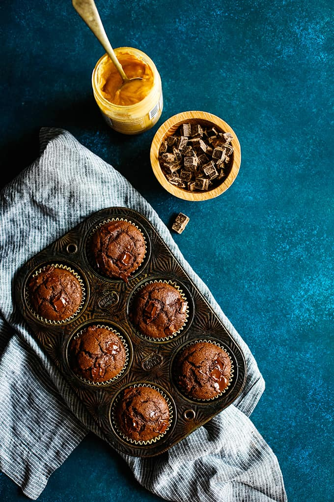 A muffin tin of Peanut Butter Mocha Chocolate Chip Muffins rests on a striped napkin surrounded by a bowl of chocolate chunks and a jar of peanut butter.