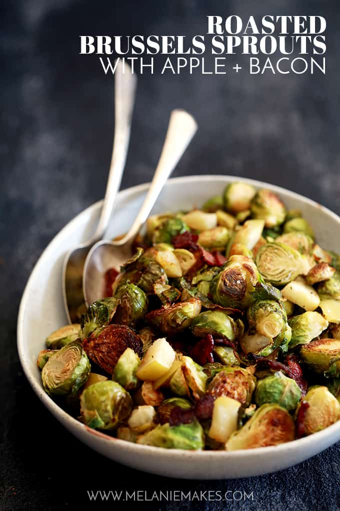 A bowl of Roasted Brussels Sprouts with Apple and Bacon with two spoons sits on a dark background.