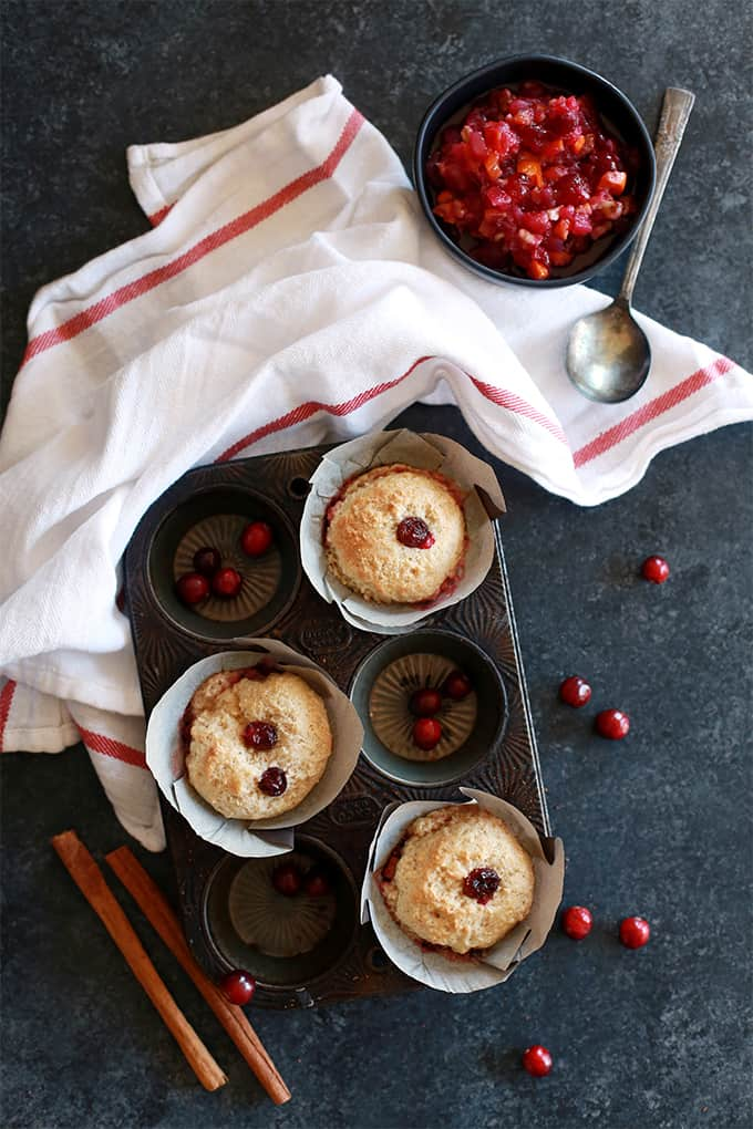 Cranberry Cobbler Muffins rest in baking tin on a dark surface surrounded by a napkin, cranberry sauce, cranberries and cinnamon sticks.