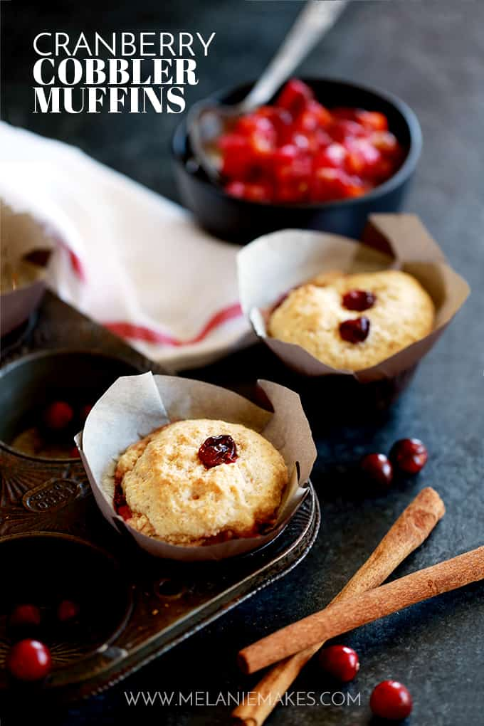 Two Cranberry Cobbler Muffins along with a baking tin, a bowl of cranberry sauce, cinnamon sticks and cranberries sit on a dark surface.