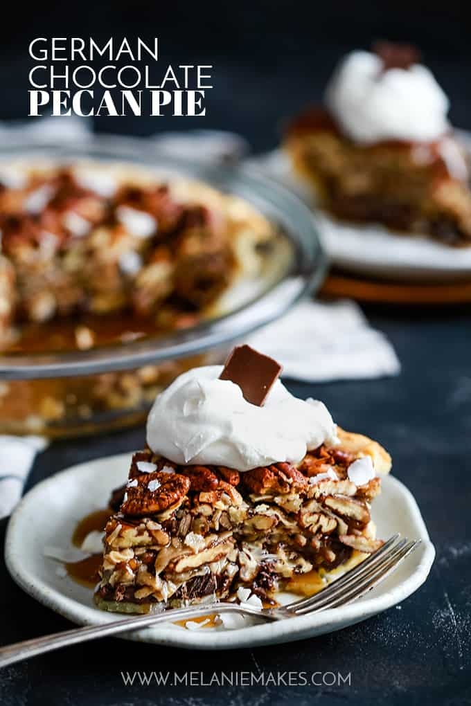 A slice of German Chocolate Pecan Pie sits on a white plate with a fork in front of a pie plate and another plate with a slice of pie.