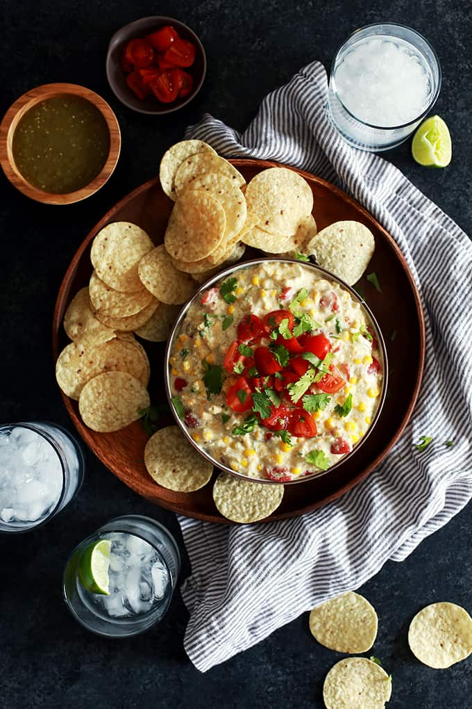 A bowl of Slow Cooker Salsa Verde Corn Dip Cream on a wooden tray with tortilla chips.  Surrounded by a striped napkin, drinks and bowls of salsa and tomatoes.