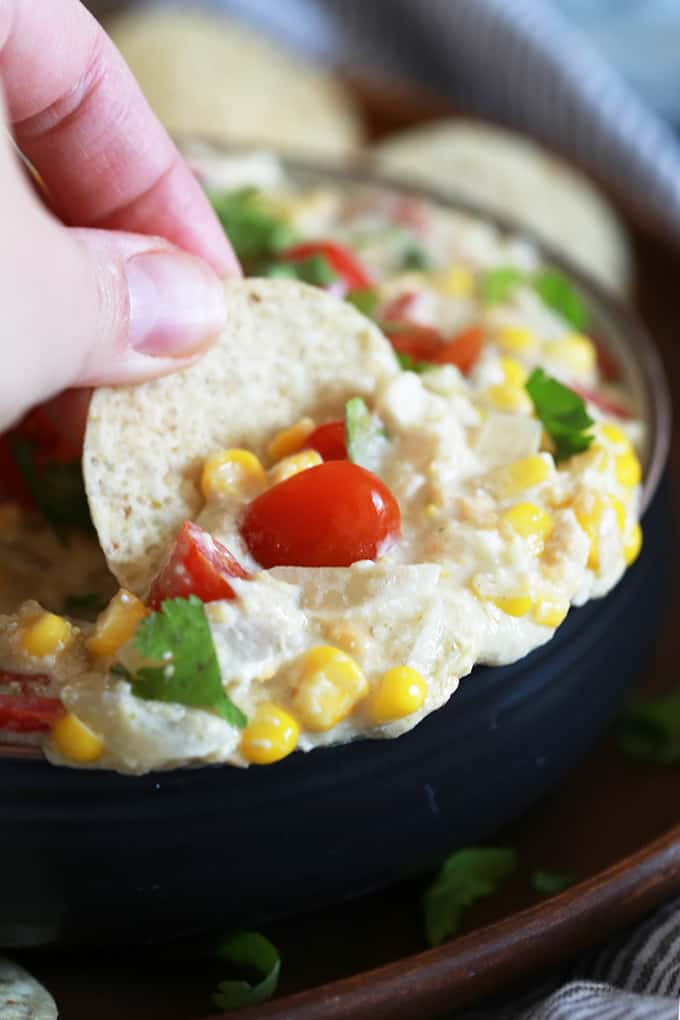 A hand dips a tortilla chip into a bowl of Slow Cooker Salsa Verde Corn Dip.