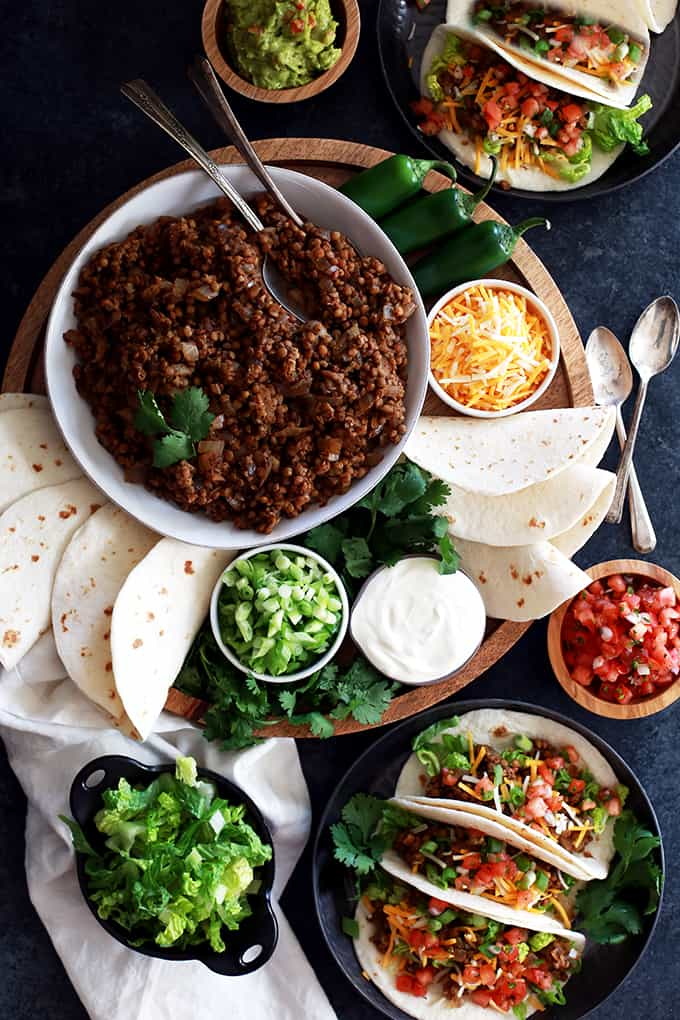 An overhead shot of two plates of Slow Cooker Lentil and Brown Rice Tacos with a platter of taco toppings.