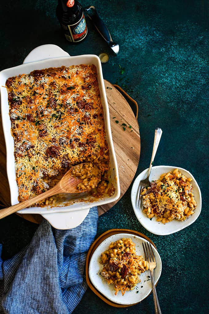 A baking dish of Bacon Crusted Beer Mac and Cheese sits on a wooden tray alongside two white plates.
