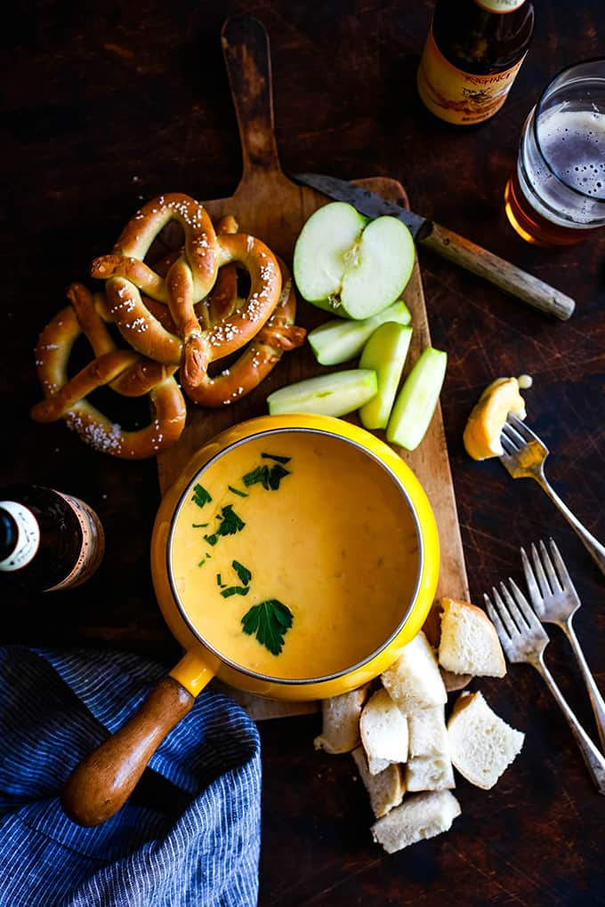 Beer Cheese Fondue on a wooden board surrounded by pretzels, apples and bread.
