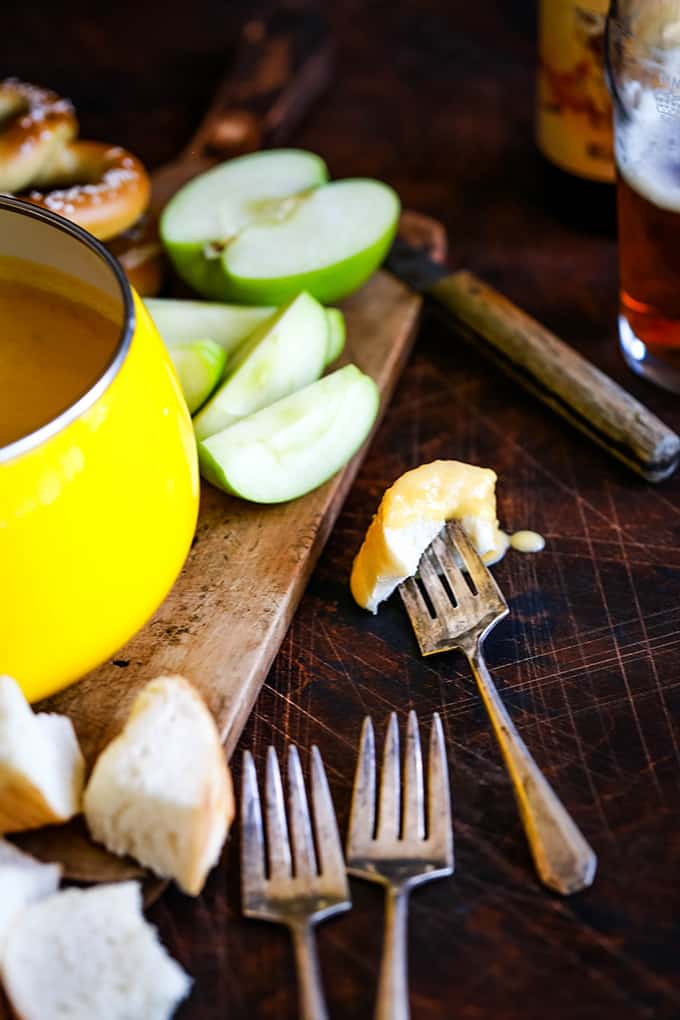 A fork with a piece of bread dipped into Beer Cheese Fondue.