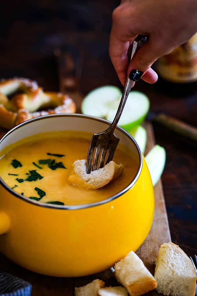 A hand dips a fork with a piece of bread into a fondue pot of Beer Cheese Fondue.