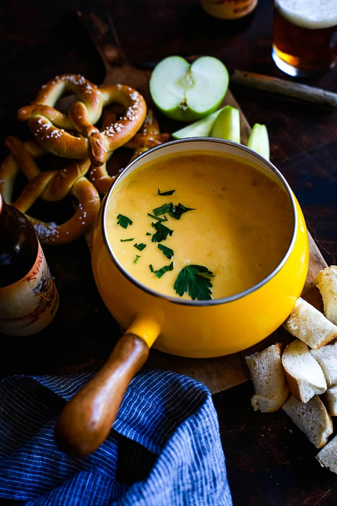 A fondue pot full of Beer Cheese Fondue surrounded by pretzels, bread and apples.