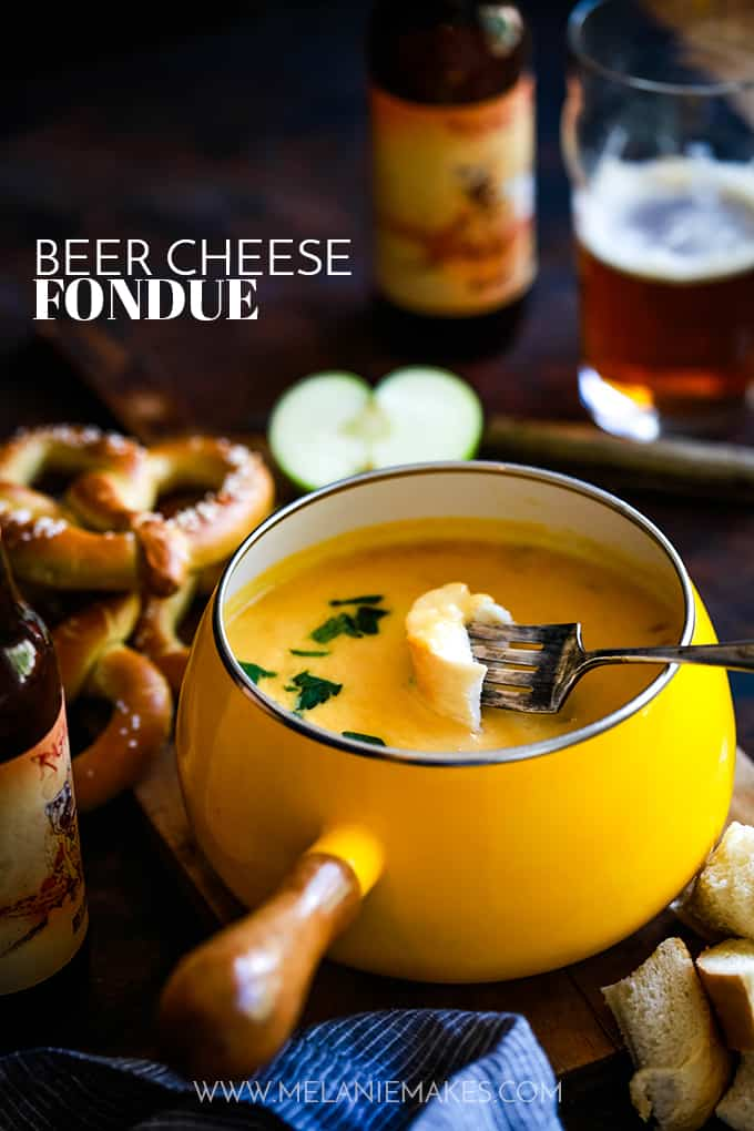 A fondue pot full of Beer Cheese Fondue with a fork dipping a piece of bread.