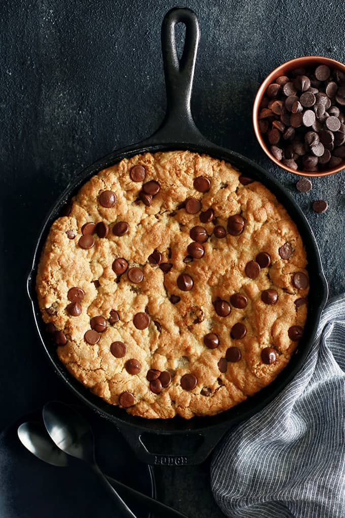 An overhead view of a Deep Dish Chocolate Chip Skillet Cookie surrounded by a striped napkin, spoons, and a bowl of chocolate chips.
