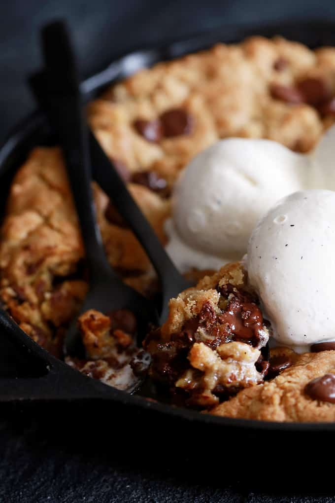 A Deep Dish Chocolate Chip Skillet Cookie with a fork removing a bite.