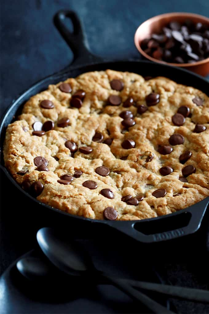 A Deep Dish Chocolate Chip Skillet Cookie with two black spoons and a bowl of chocolate chips.
