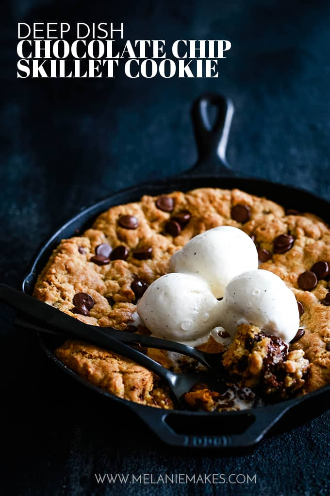 Two forks in a Deep Dish Chocolate Chip Skillet Cake topped with scoops of vanilla ice cream.