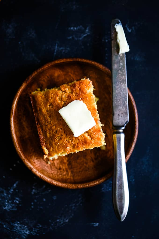 A slice of Simple Sweet Cornbread topped with a pat of butter on a wooden plate. A knife sits on the right edge of the plate.