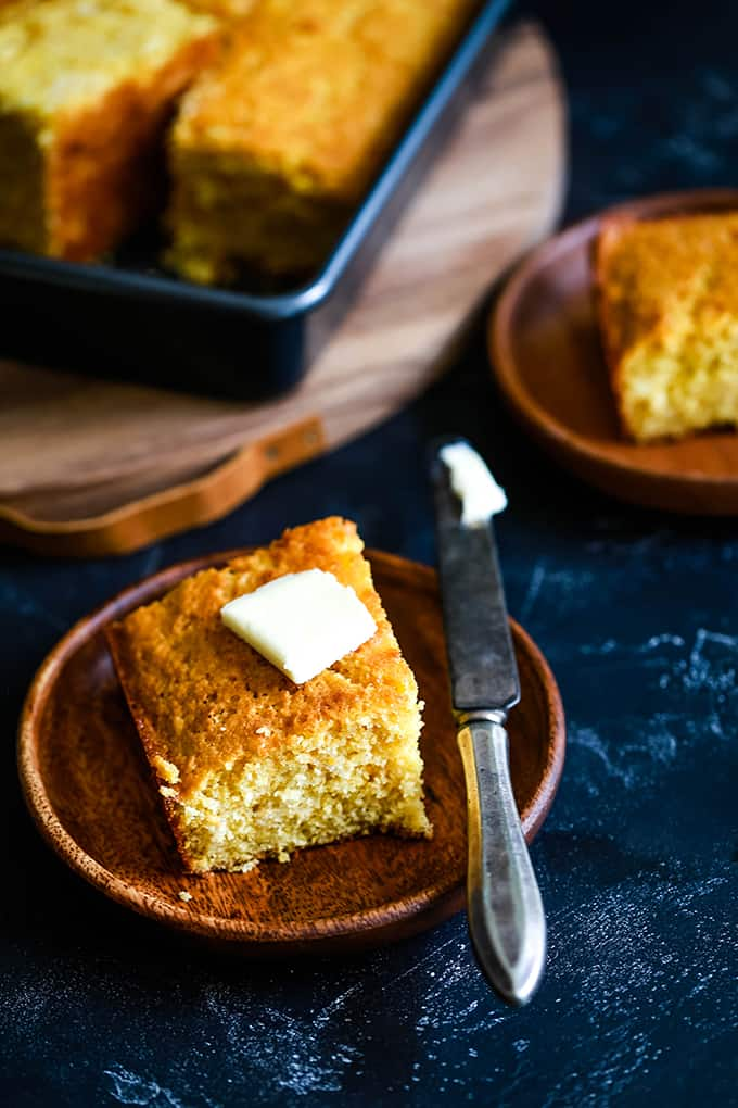 A wooden plate with a piece of Simple Sweet Cornbread topped with a pat of butter and a knife on the side of the plate. A pan of cornbread and another plate are in the background.