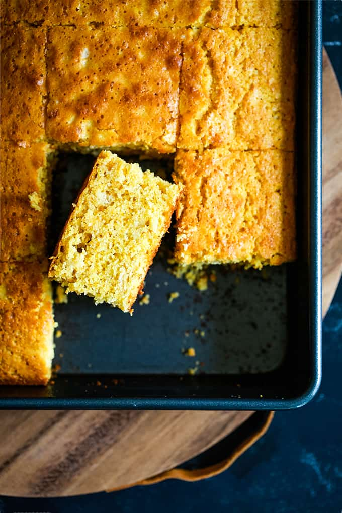 A pan of Simple Sweet Cornbread with two slices removed, sitting on a wooden serving board.