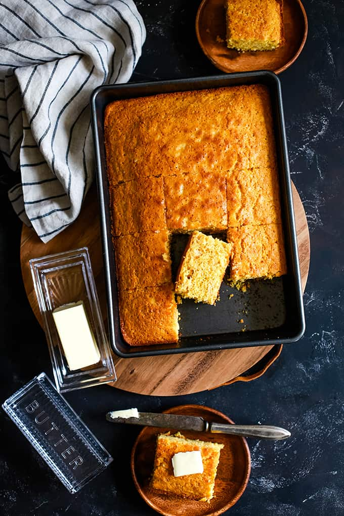 A pan of Simple Sweet Cornbread that is sliced and on a wooden serving board. Two wooden plates each hold a slice of cornbread.