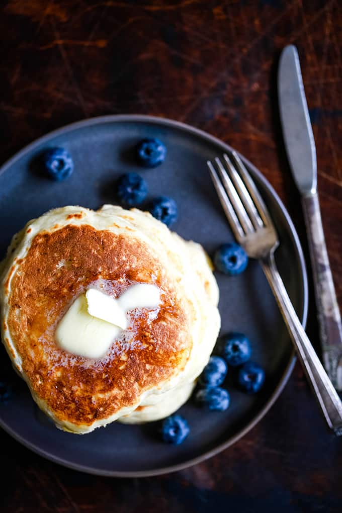 An overhead view of a stack of the Best Buttermilk Pancakes topped with a melting pat of butter.