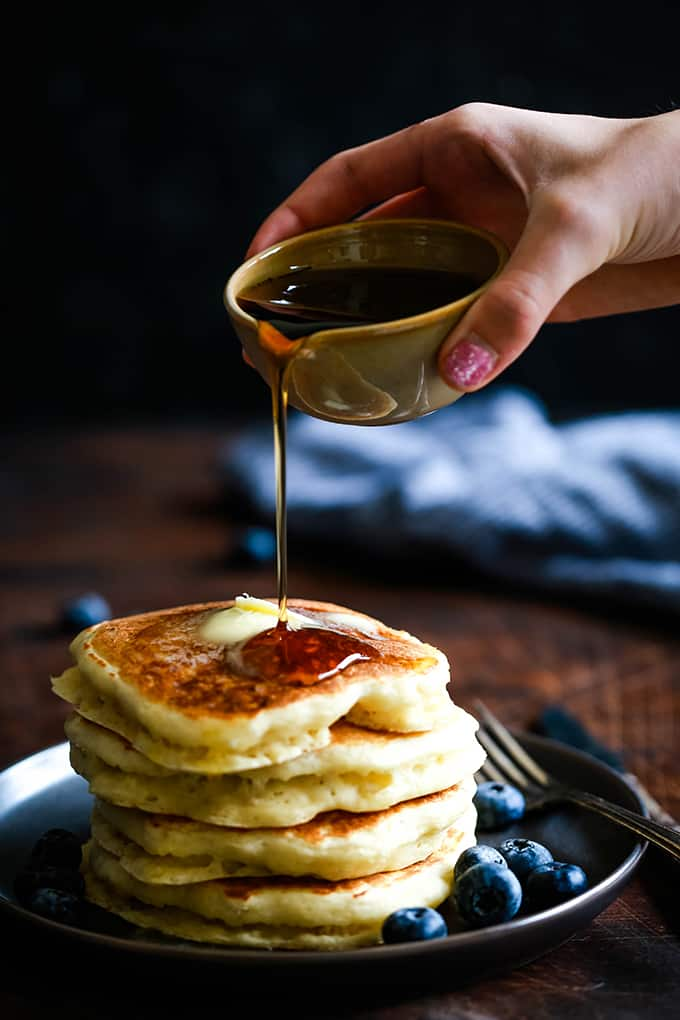 A hand pours syrup onto a stack of the Best Buttermilk Pancakes.