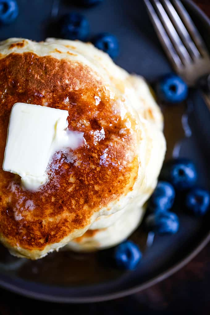 Butter melts on a stack of the Best Buttermilk Pancakes surrounded by blueberries.